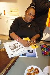 Mama Ali signing books at a Luxury Chamber Media Group Event
